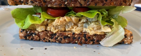 chickpea salad sandwich on seeded bread with lettuce and tomato