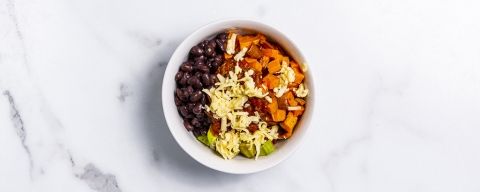 bowl of rice topped with black beans, sweet potato, avocado, and cheese