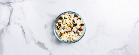 bowl of popcorn with nuts, seeds, and dried fruit
