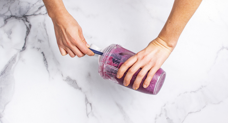 smoothie being taken out of a blender cup
