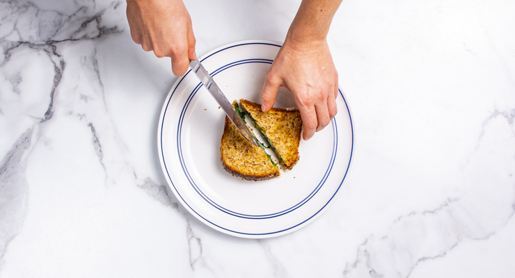 person cutting into a grilled cheese sandwich